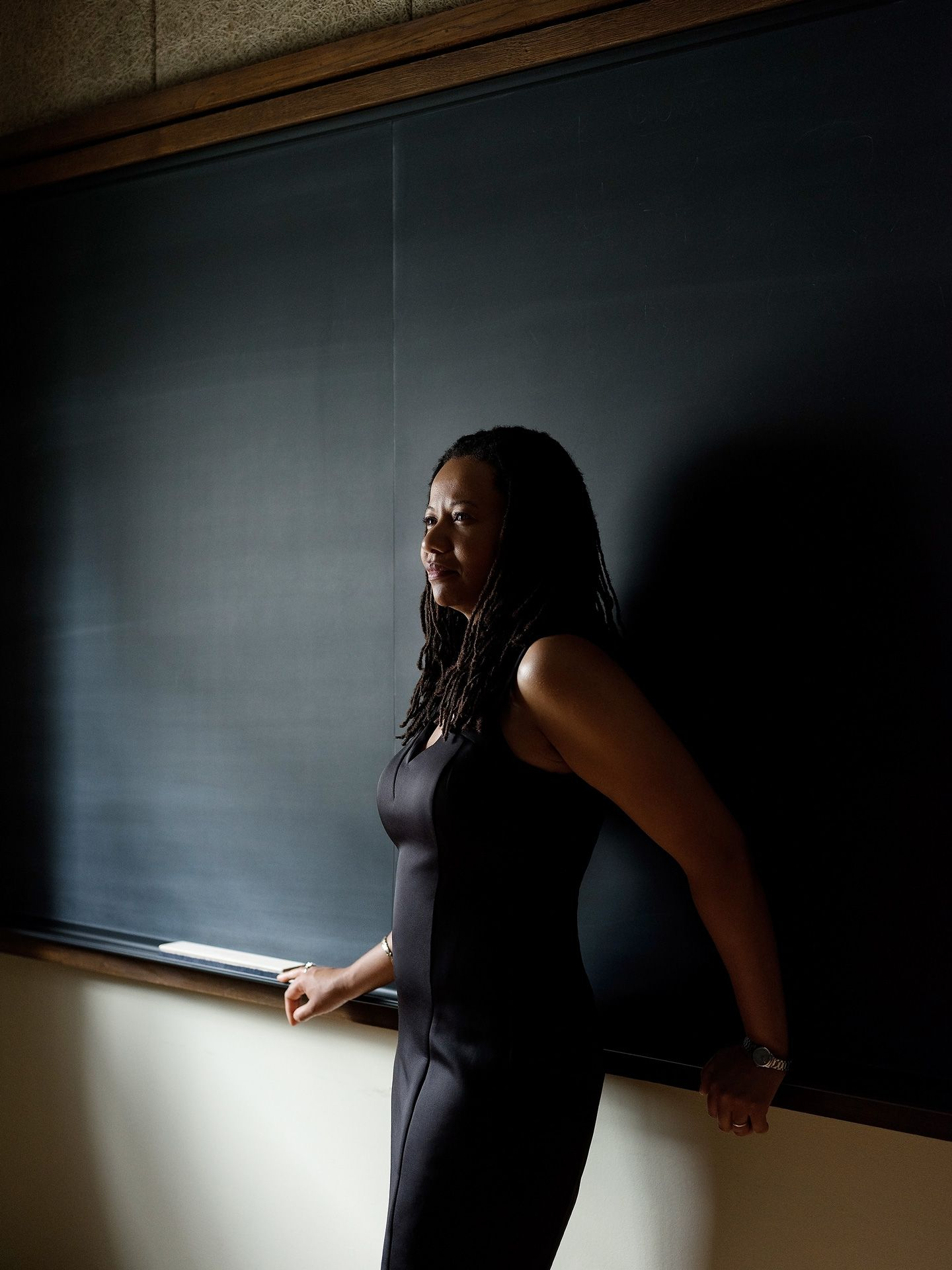 Charmaine Nelson black woman university teacher leaning against clean black board wearing fitting black dress smiling face in the sun by Guillaume Simoneau for University Affairs magazine