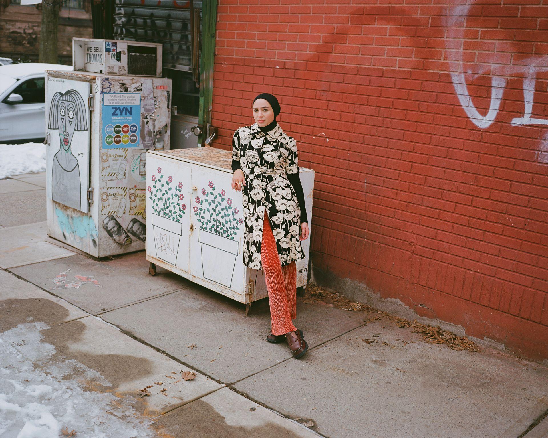 Femme accoté sur boite extérieur devant mur brique rouge New York