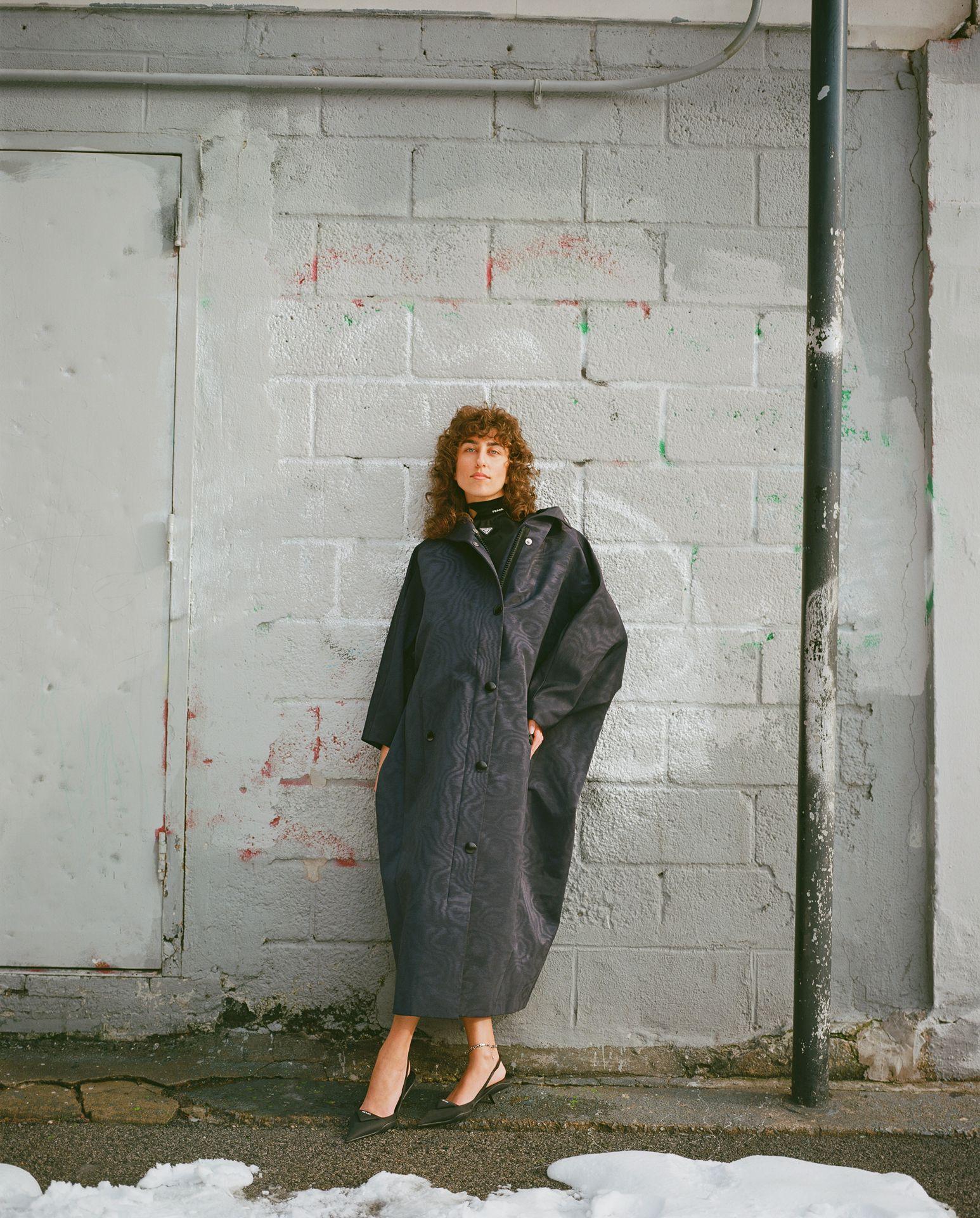 Femme grand manteau noir accoté sur mur extérieur New York