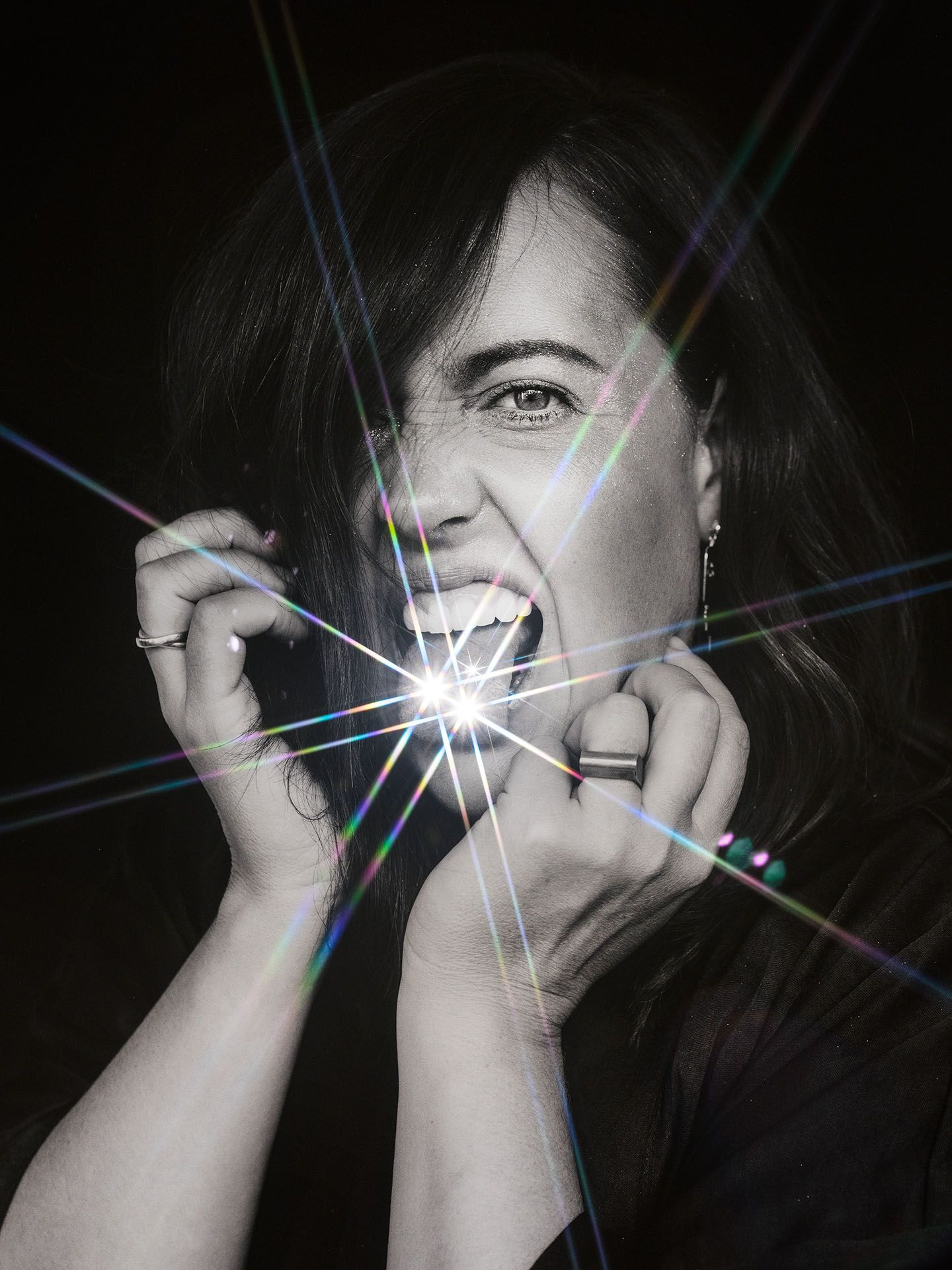 portrait of Ariane Moffatt in black and white sticking tongue out bling on tongue on black background by Jocelyn Michel for Voir
