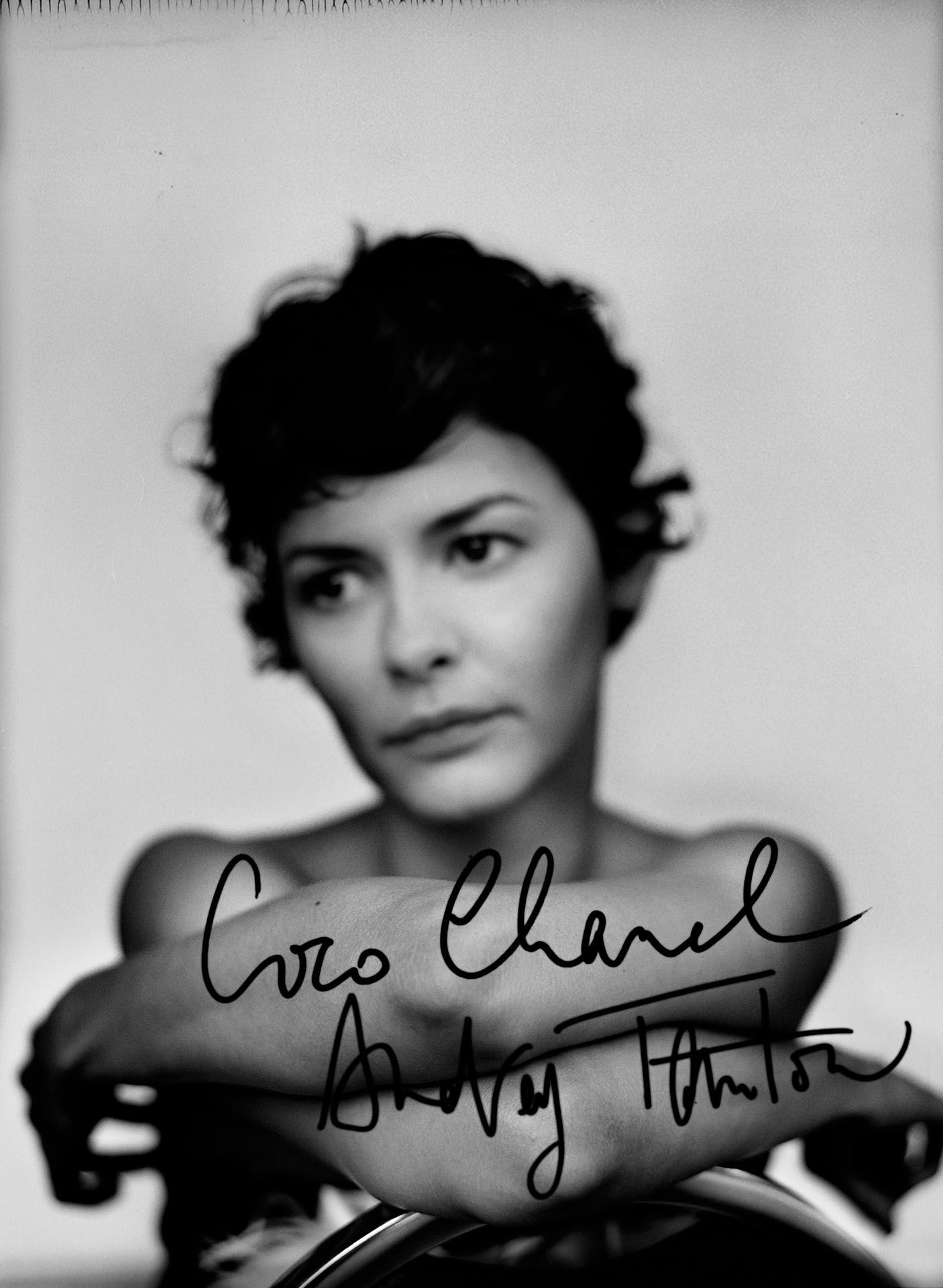 blurred portrait of Audrey Tautou in black and white sitting backward on chair on white background white autograph of coco chanel in foreground by Jocelyn Michel for Voir