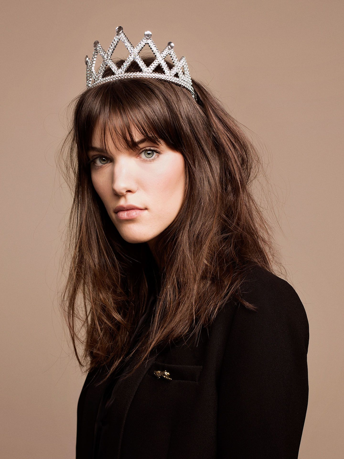 portrait of singer Charlotte Cardin looking at camera dressed in black turtleneck wearing plastic crown on beige background by Jocelyn Michel for Voir