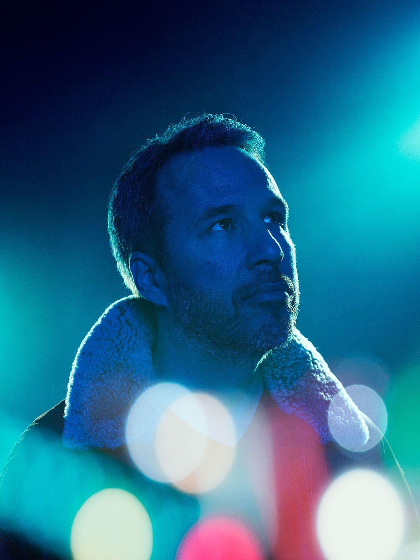 portrait of Denis Villeneuve in blue lighting on blue background and bokeh effect by Jocelyn Michel for Voir