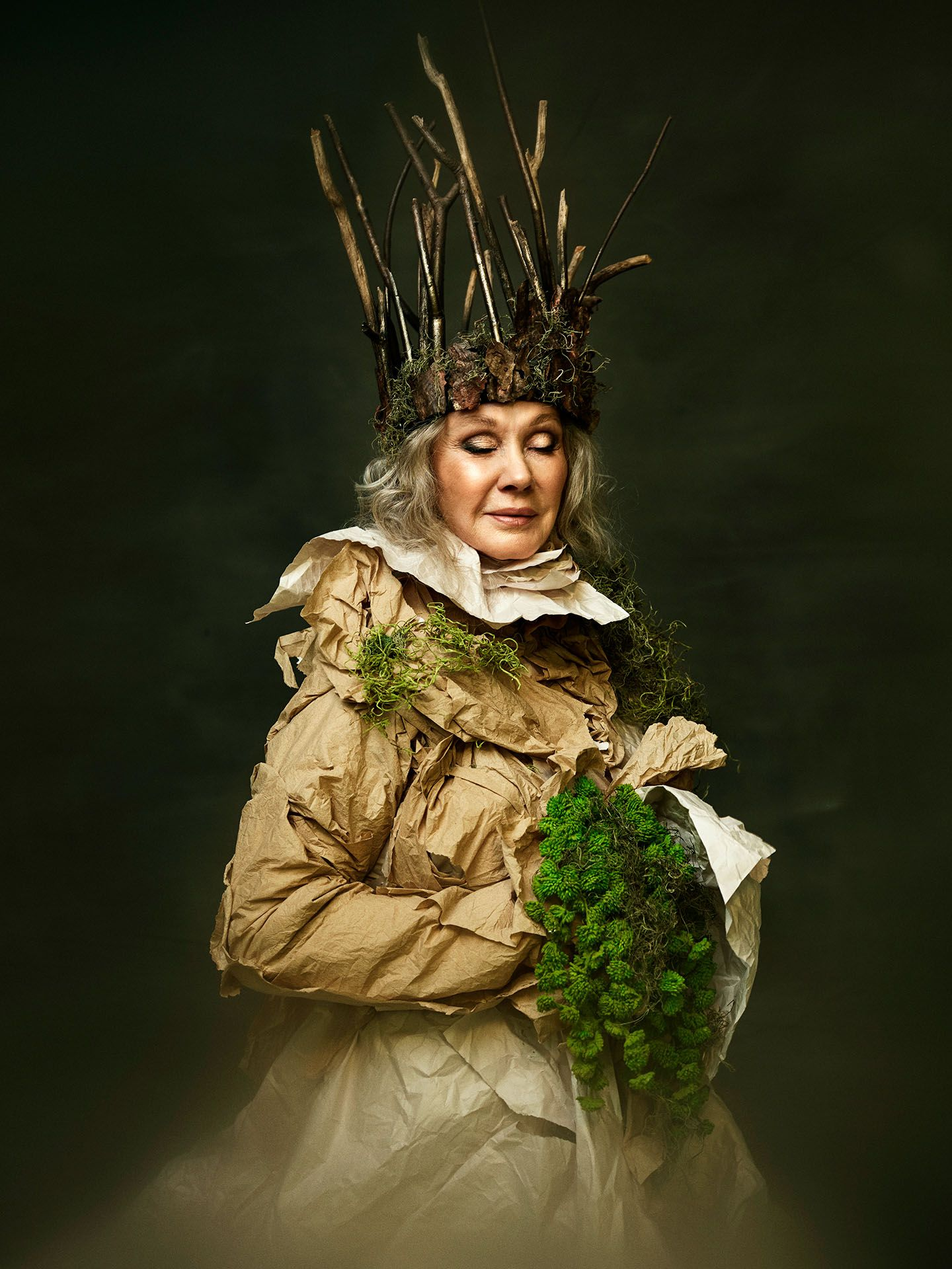 portrait of Diane Dufresne dressed in long brown paper dress with wood branches crown and moss bouquet by Jocelyn Michel for Voir