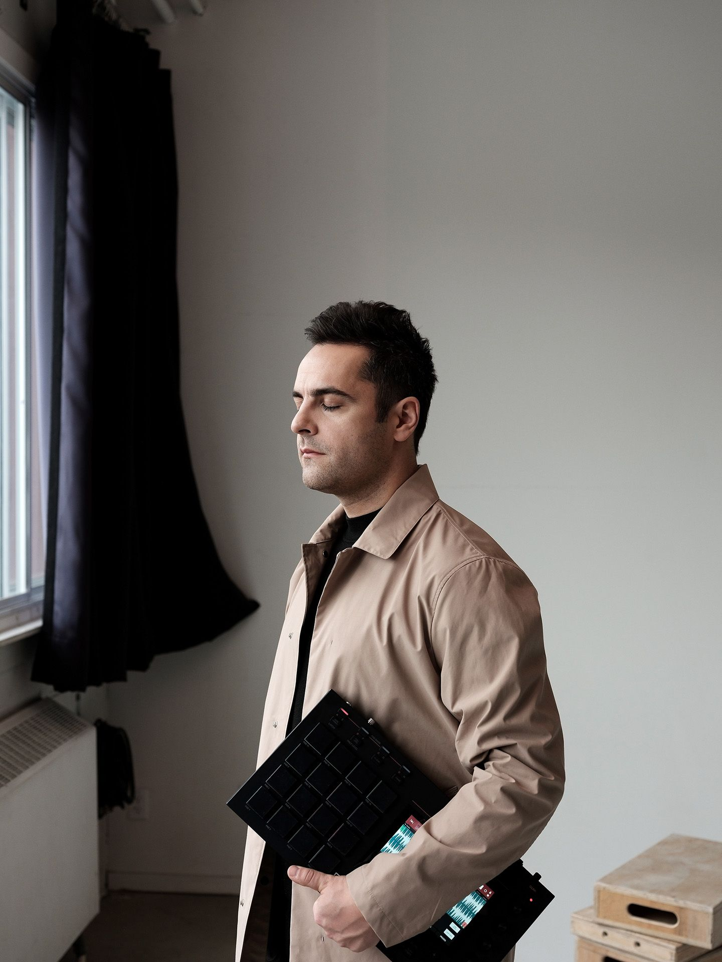 close up of singer Dumas facing a window with his eyes closed holding a synthetiser wearing light brown coat with black shirt photographed in studio by Guillaume Simoneau for Voir's magazine covers
