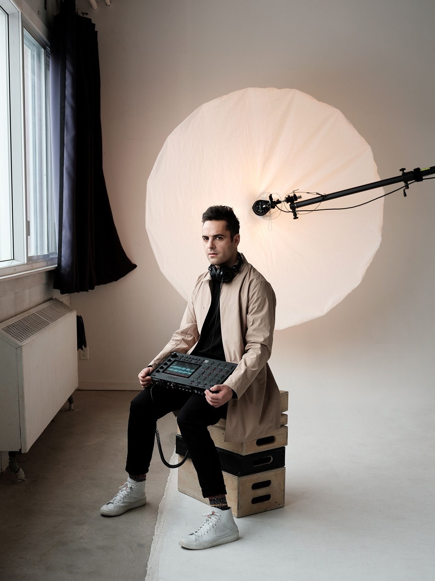 singer Dumas sitting on wooden crates looking at camera holding a synthetiser on his lap wearing light brown coat with black shirt photographed in studio by Guillaume Simoneau for Voir's magazine covers