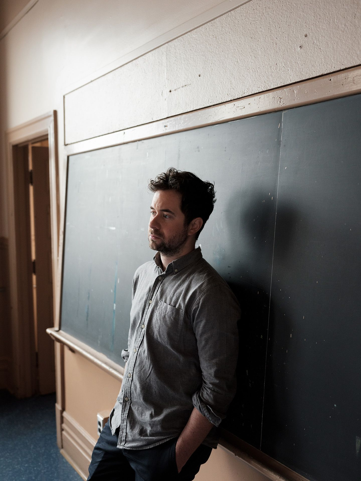 singer Jean-Michel Blais posing against black chalkboard with his hands in his pockets wearing grey shirt black pants photographed by Guillaume Simoneau for Voir's magazine cover