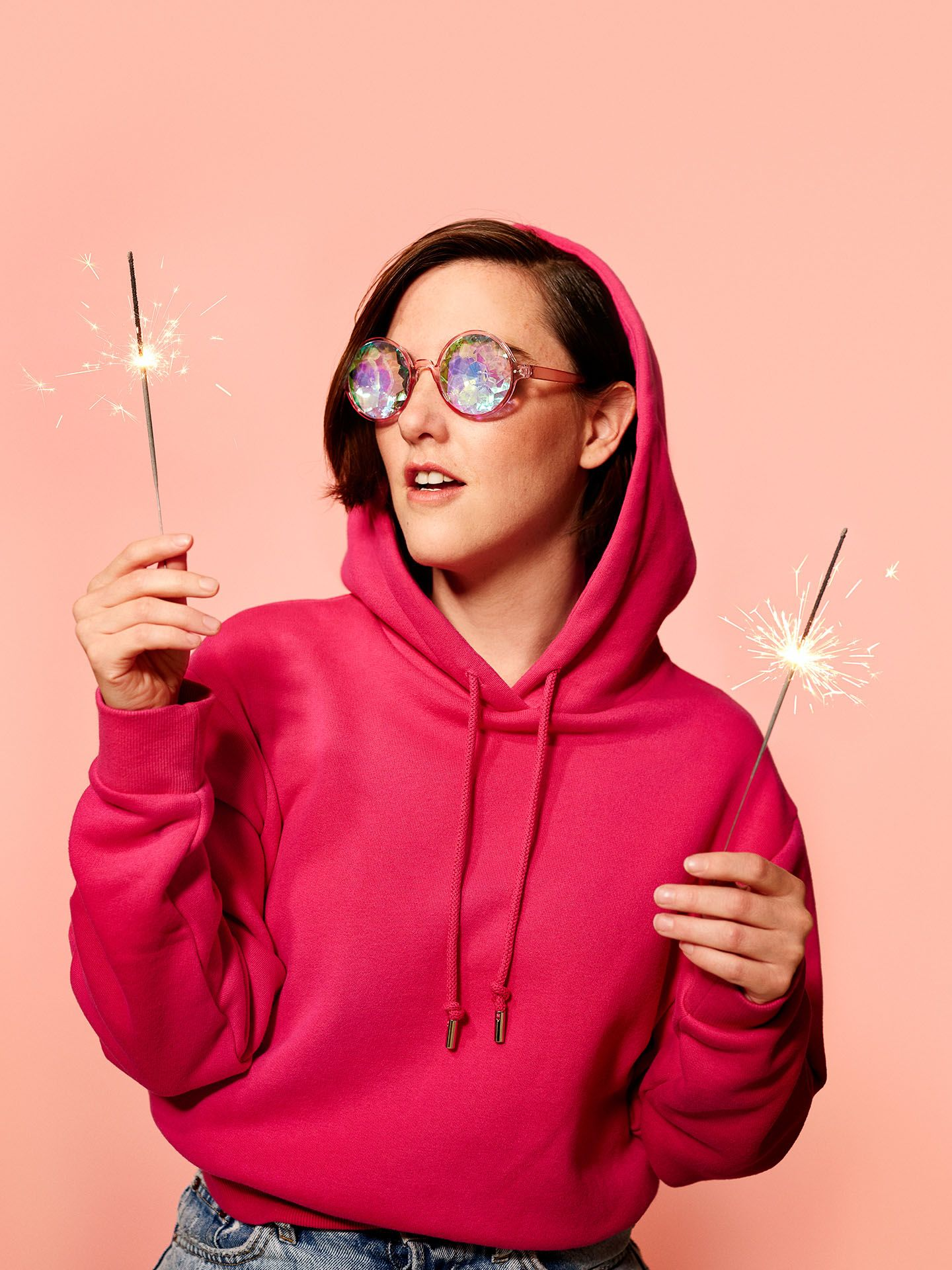 portrait of Florence Longpre wearing bright pink hoodie holding candle sticks on light pink background by Jocelyn Michel for Voir