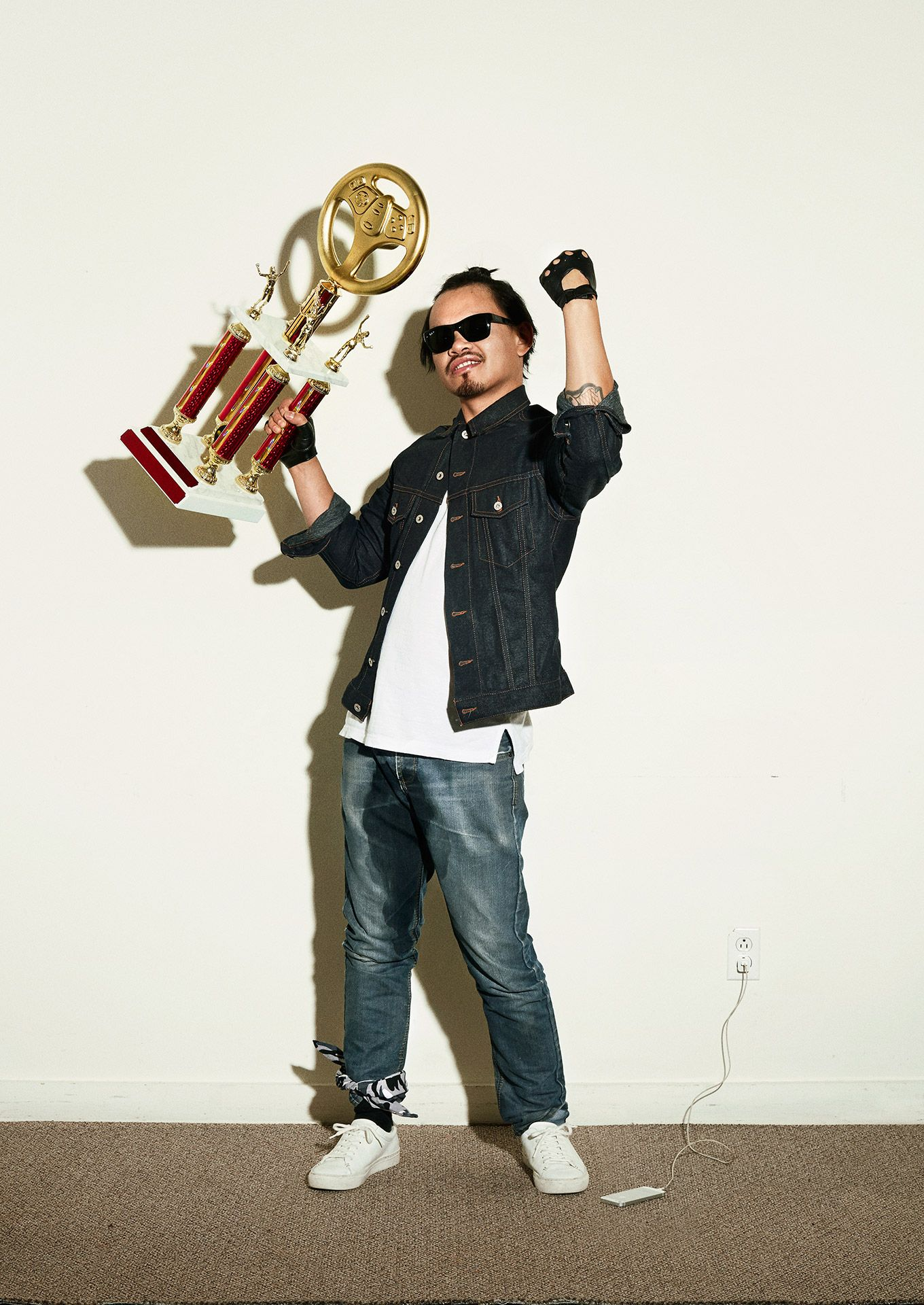 archetype of asian gamer boy wearing sunglasses peed in his pants holding trophy victoriously by Jocelyn Michel for Vovlan with DentsuBos