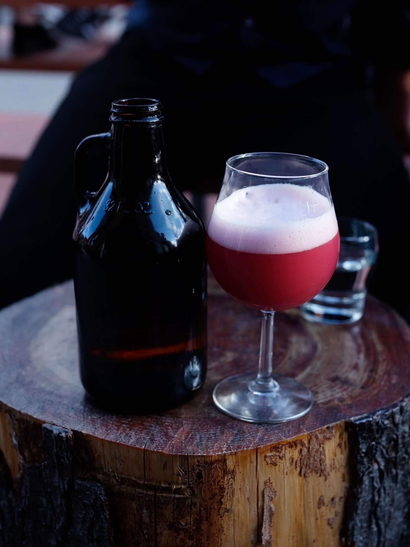 glass of cherry tinted beer with old fashioned bottle next to it on wood piece photographed by Guillaume Simoneau as part of Off Duty Montreal series for The Wall Street Journal magazine