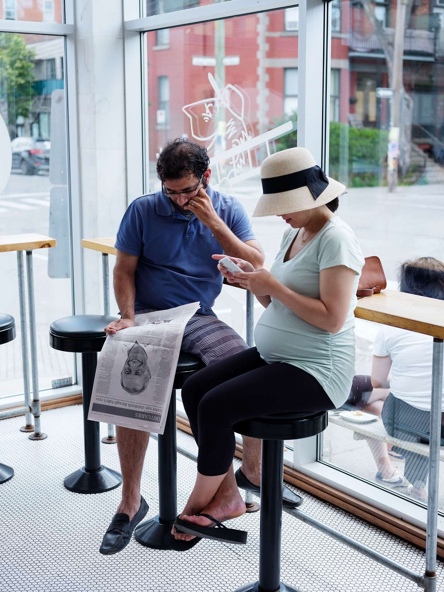 couple sitting on bar stools at cafe woman on her phone and man reading a newspaper photographed by Guillaume Simoneau as part of Off Duty Montreal series for The Wall Street Journal magazine