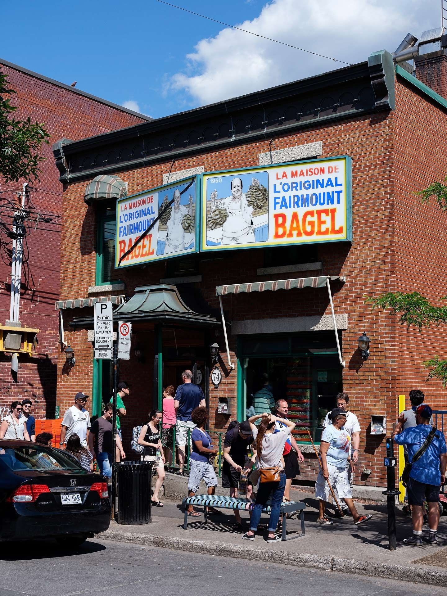 front window of iconic Fairmount Bagels shop with line of people coming out photographed by Guillaume Simoneau as part of Off Duty Montreal series for The Wall Street Journal magazine