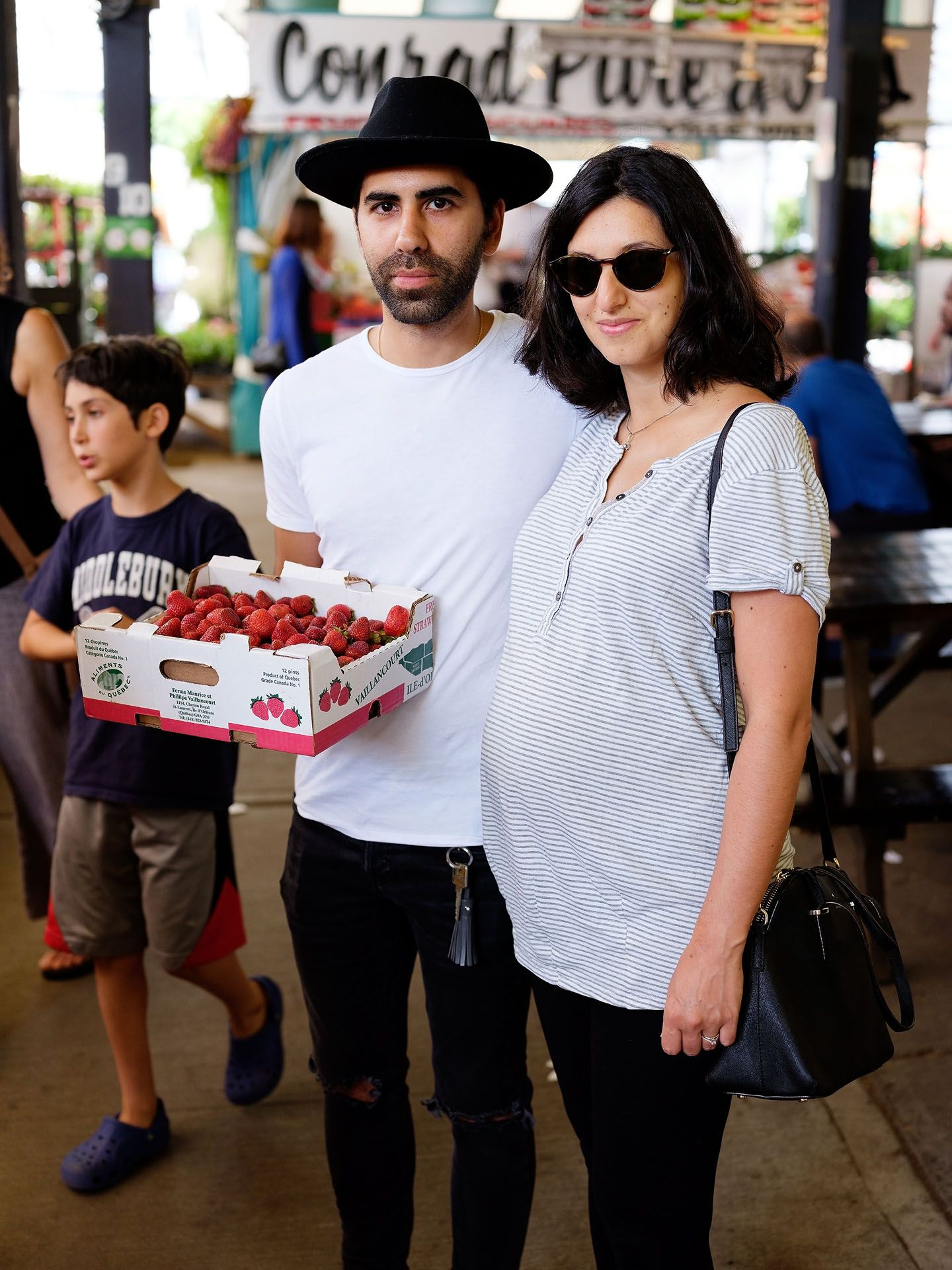 couple standing at the market holding a crate of strawberries looking at camera photographed by Guillaume Simoneau as part of Off Duty Montreal series for The Wall Street Journal magazine