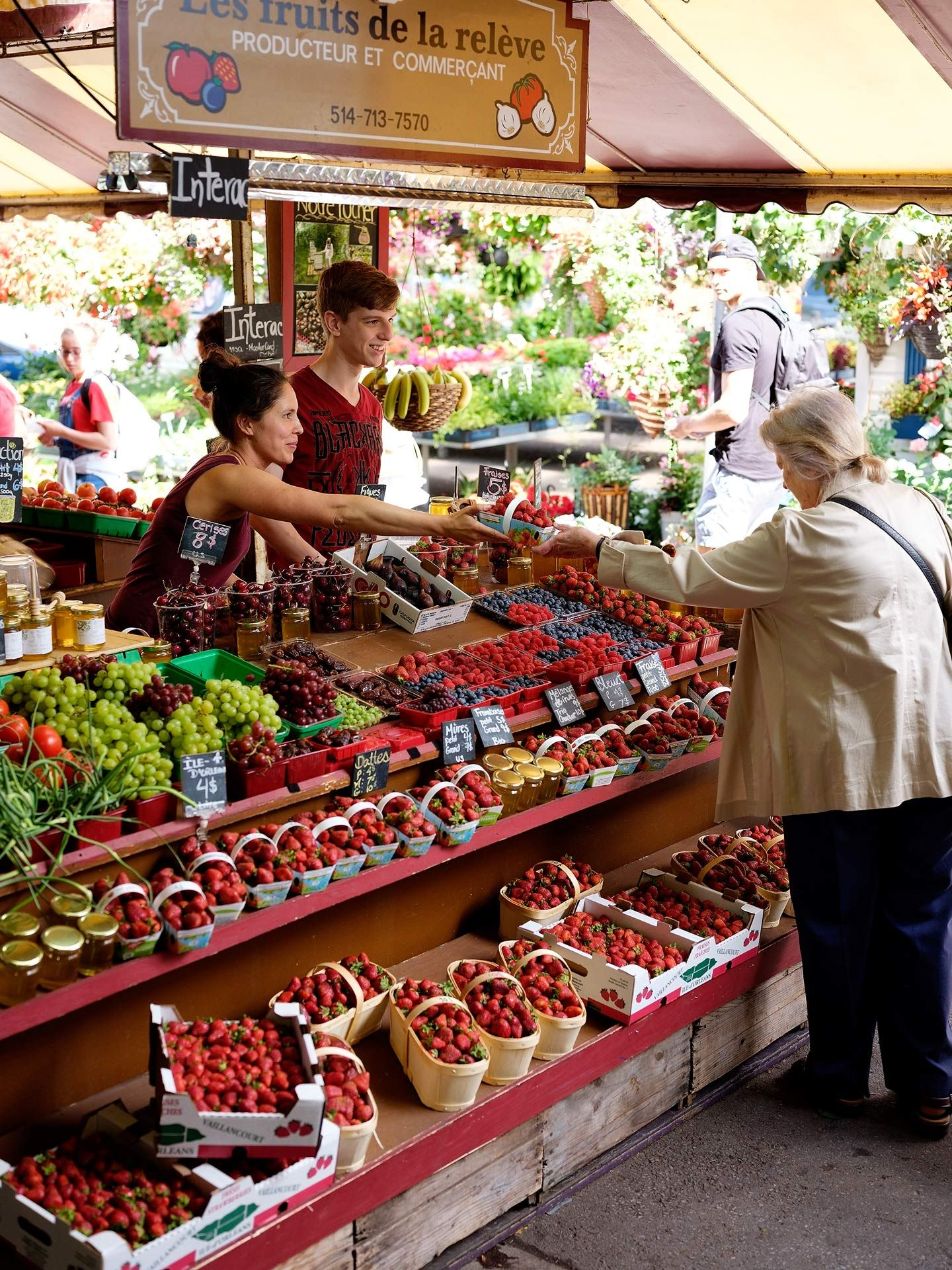fresh fruits market stall showcasing baskets of strawberries raspberries blueberries grapes cherries and jars of honey with two vendors talking to an elderly woman photographed by Guillaume Simoneau as part of Off Duty Montreal series for The Wall Street Journal magazine