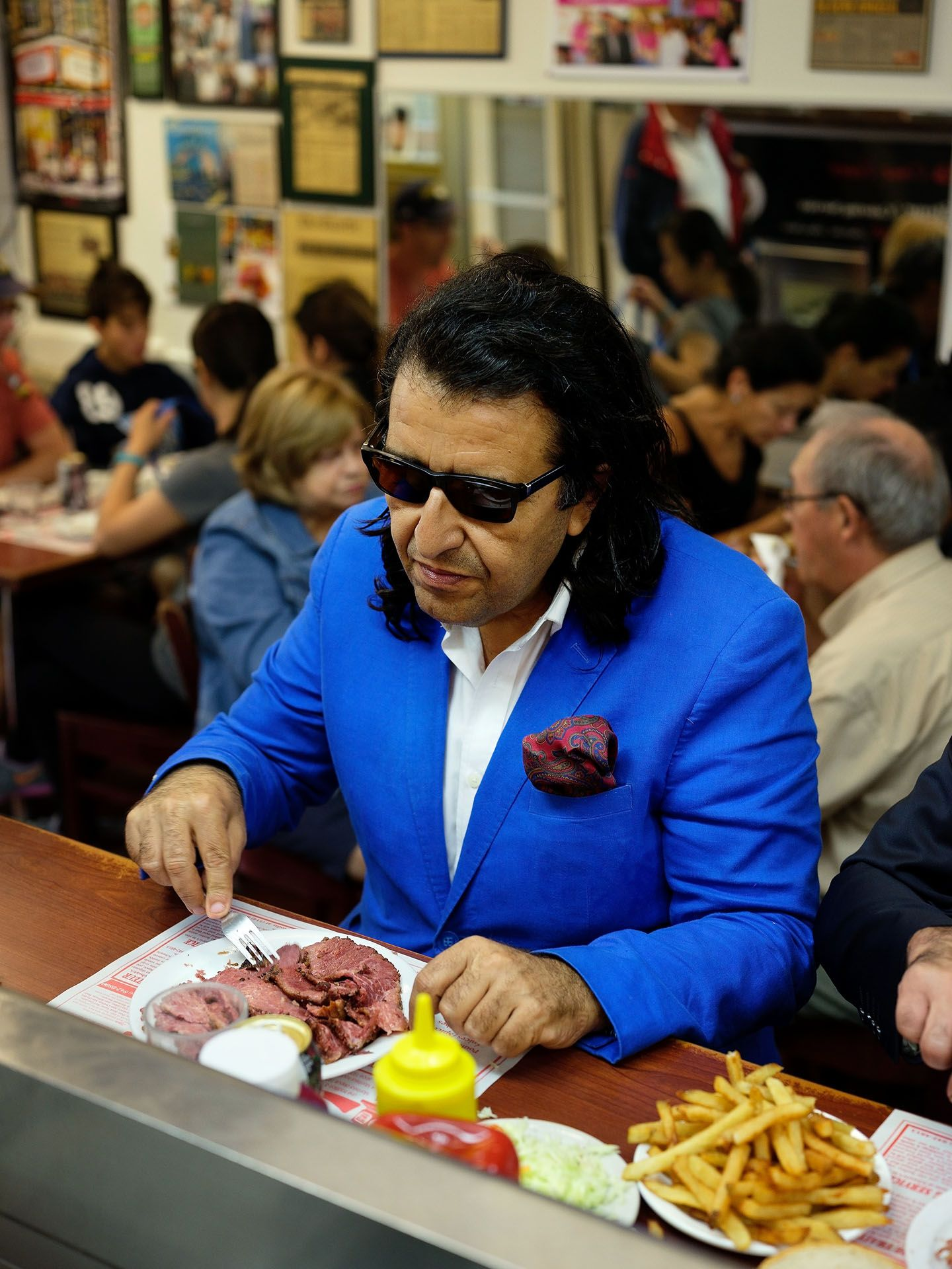 man sitting on counter at the dinner eating beef carpaccio with fries wearing bright blue tuxedo and sunglasses photographed by Guillaume Simoneau as part of Off Duty Montreal series for The Wall Street Journal magazine