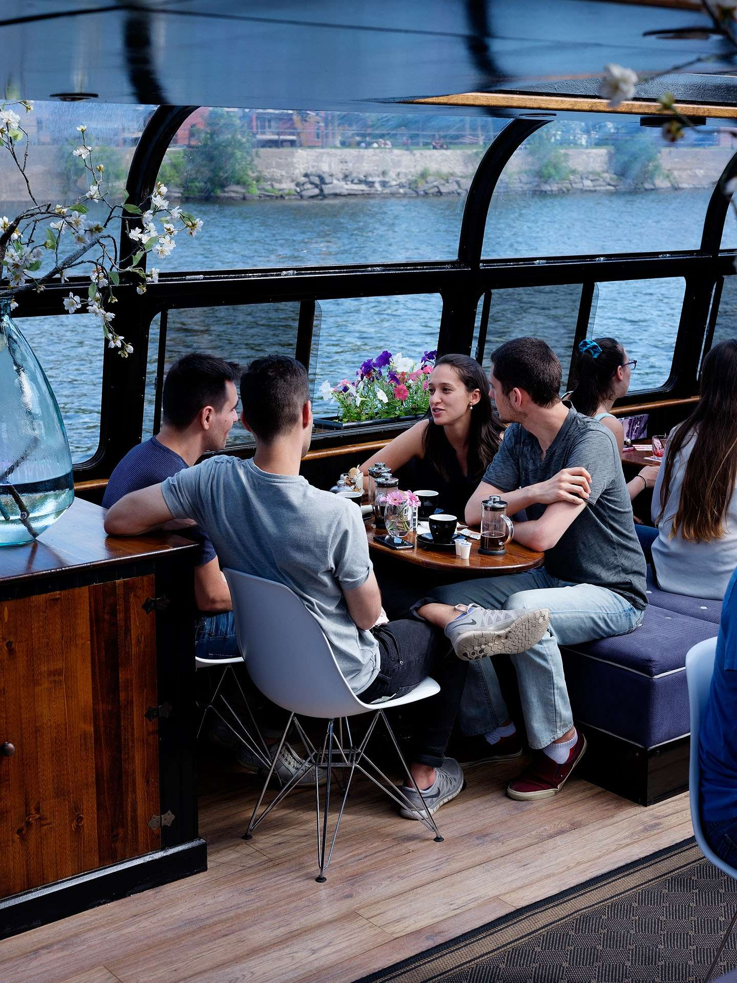 group of four sitting inside cafe inside of a river boat talking with cups of coffee in front of them photographed by Guillaume Simoneau as part of Off Duty Montreal series for The Wall Street Journal magazine