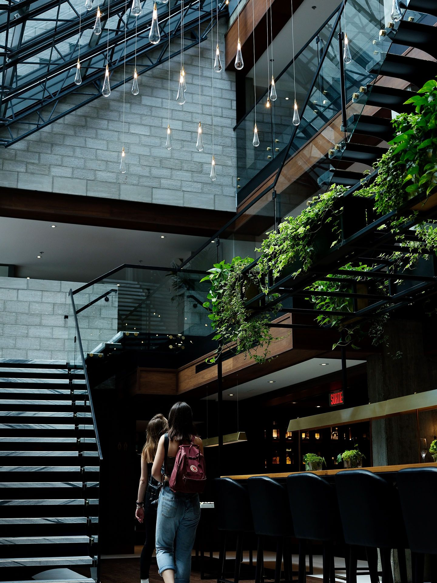 two girls walking under water drops shaped lights inside building photographed by Guillaume Simoneau as part of Off Duty Montreal series for The Wall Street Journal magazine