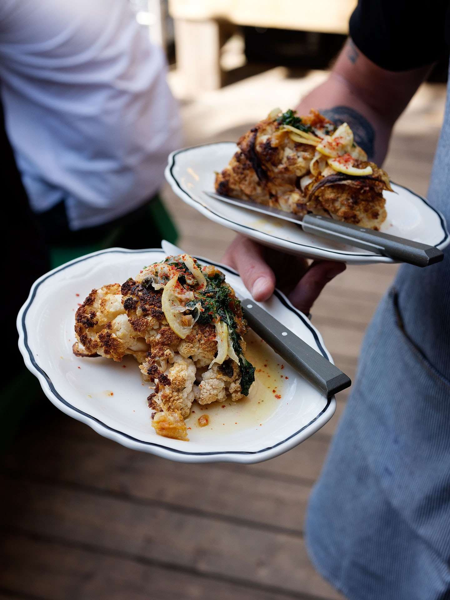 platers of roasted cauliflower held by waiter photographed by Guillaume Simoneau as part of Off Duty Montreal series for The Wall Street Journal magazine