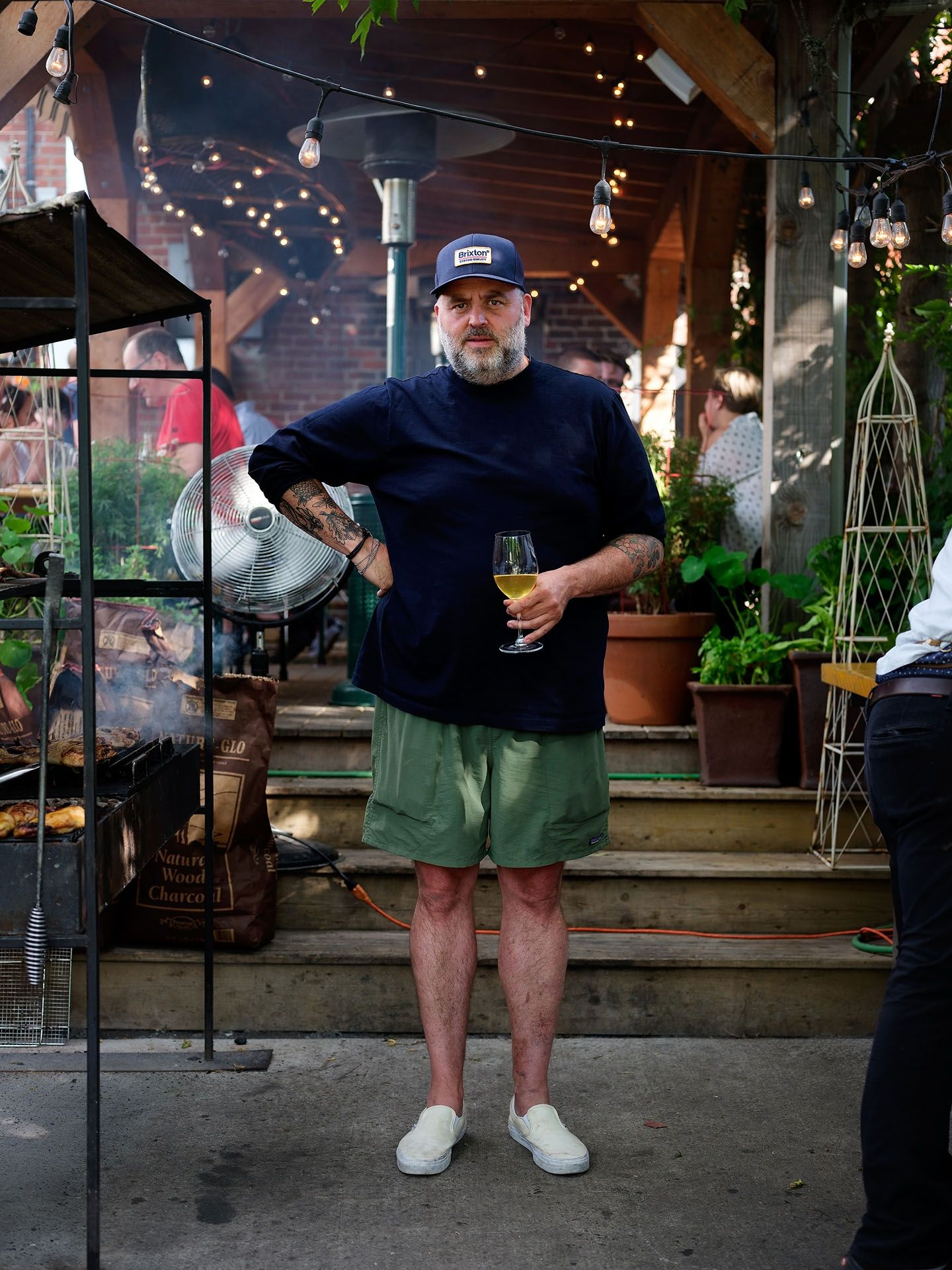 middle aged man standing next to barbecue holding glass of white wine one hand on his hip looking at camera wearing dark blue long sleeved shirt green shorts and white shoes photographed by Guillaume Simoneau as part of Off Duty Montreal series for The Wall Street Journal magazine