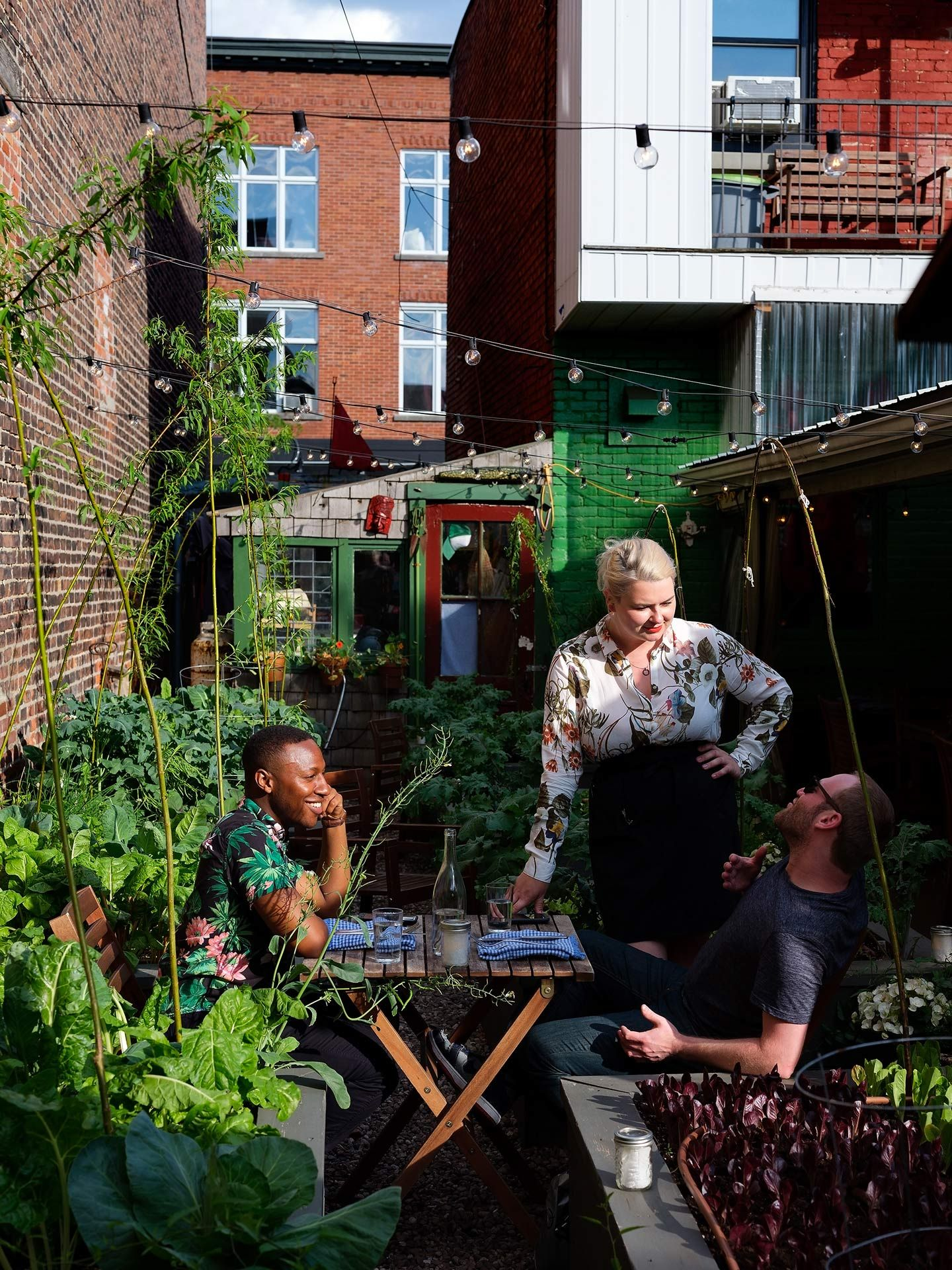 two man sitting at small wooden table in vegetable garden with woman standing with them talking photographed by Guillaume Simoneau as part of Off Duty Montreal series for The Wall Street Journal magazine