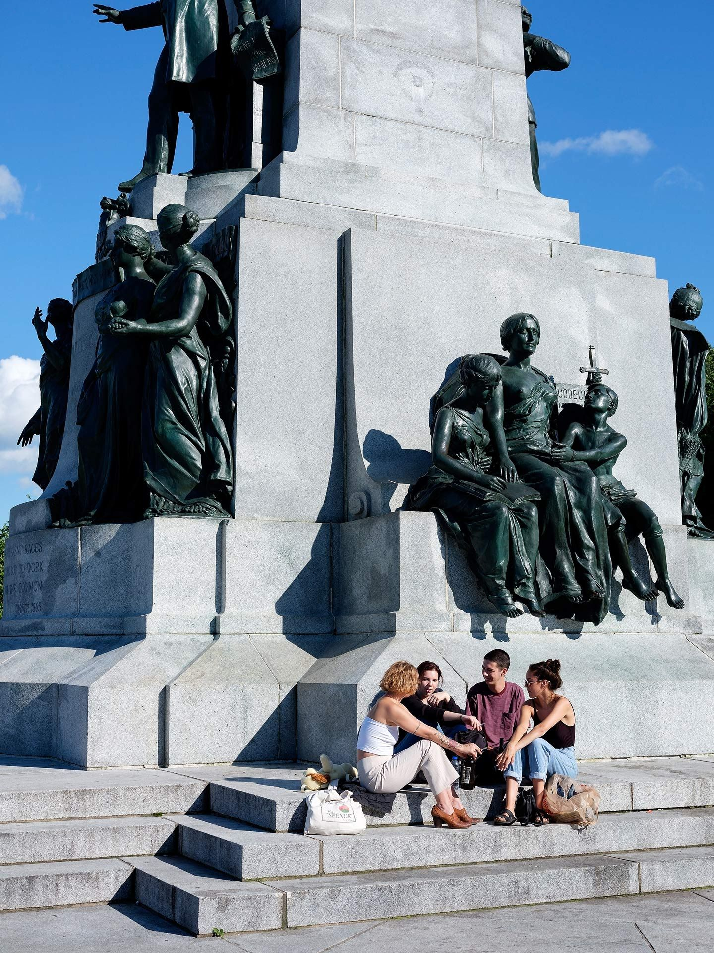 group of four sitting at the foot of Mount-Royal monument talking and laughing in the sun photographed by Guillaume Simoneau as part of Off Duty Montreal series for The Wall Street Journal magazine