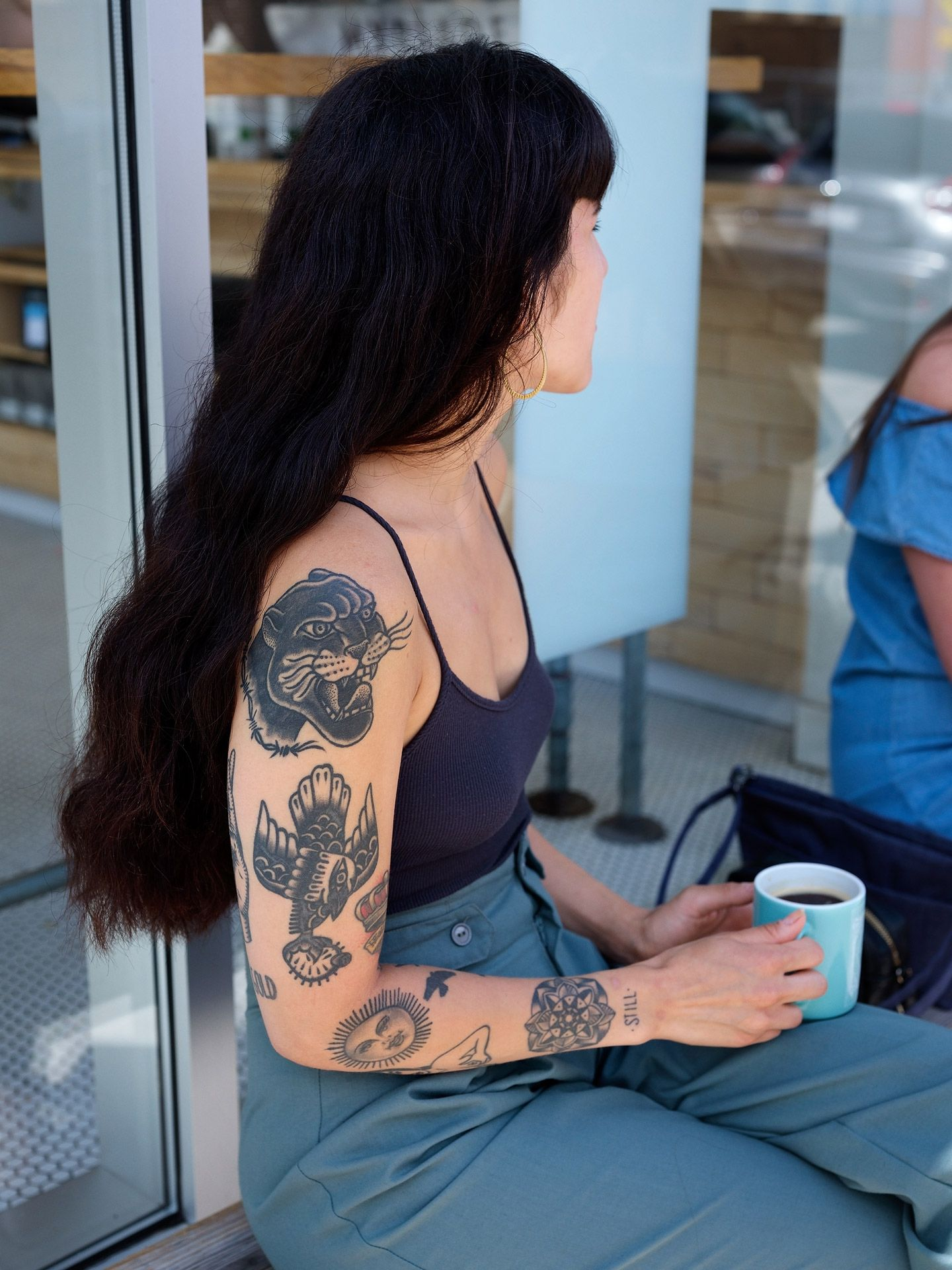 long black haired woman sitting on a bench knees crossed holding light blue cup of coffee wearing black spaghetti strap top and blue pants sporting a full sleeve of tattoos photographed by Guillaume Simoneau as part of Off Duty Montreal series for The Wall Street Journal magazine