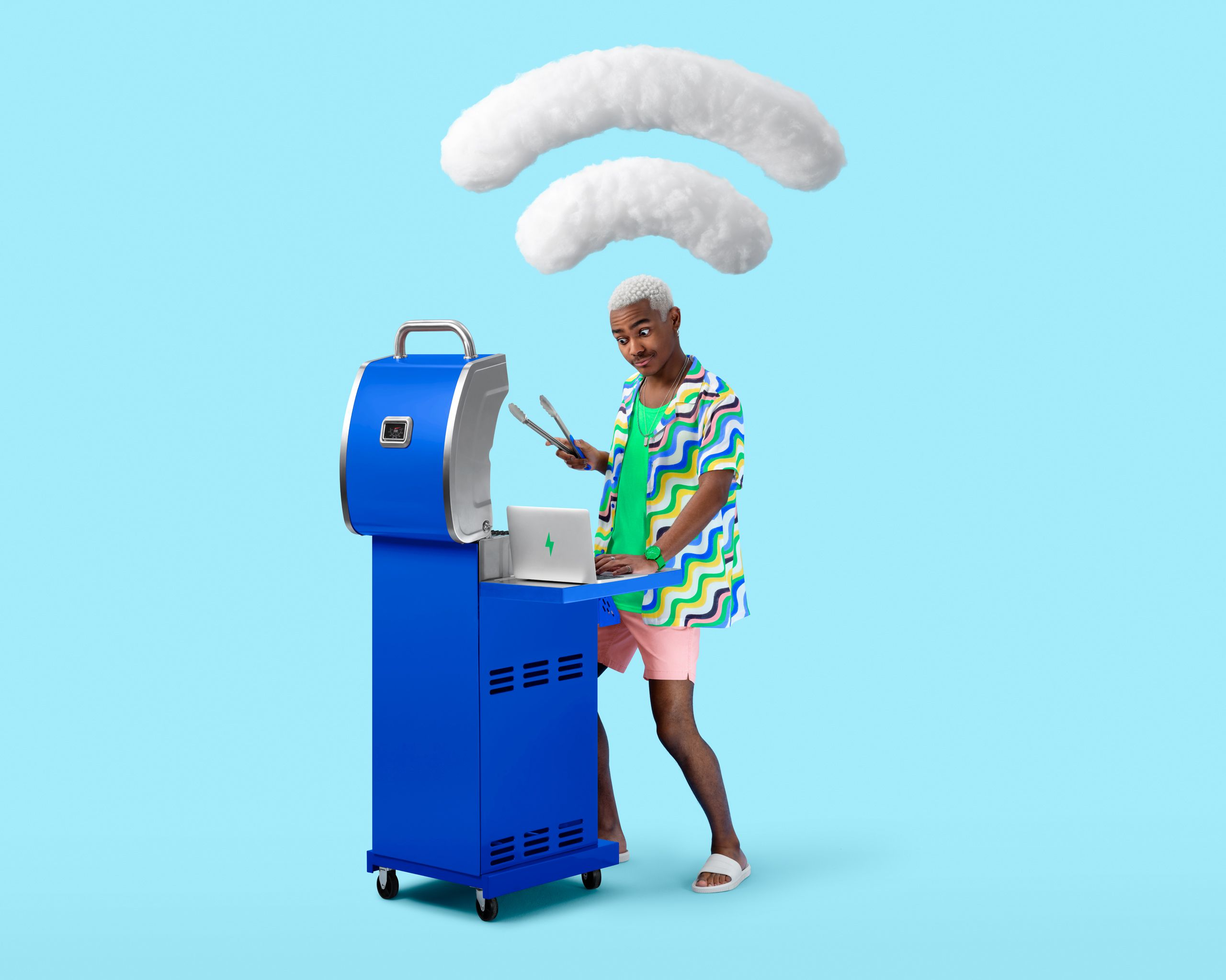 Man making a funny face has a laptop on a barbecue. There is a wifi symbol in plush clouds above the man.