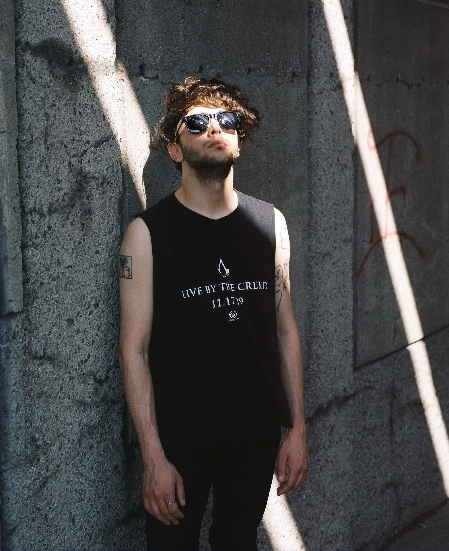 portrait of cinema director and actor Xavier Dolan wearing sunglasses and black shirt in a ray of sun by Guillaume Simoneau for The Walrus
