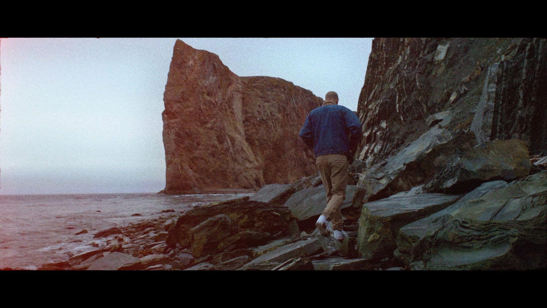 singer Yuki Dreams Again walking on rocks on the seaside wearing dark blue coat and camel pants in their promotional video filmed by Les Gamins