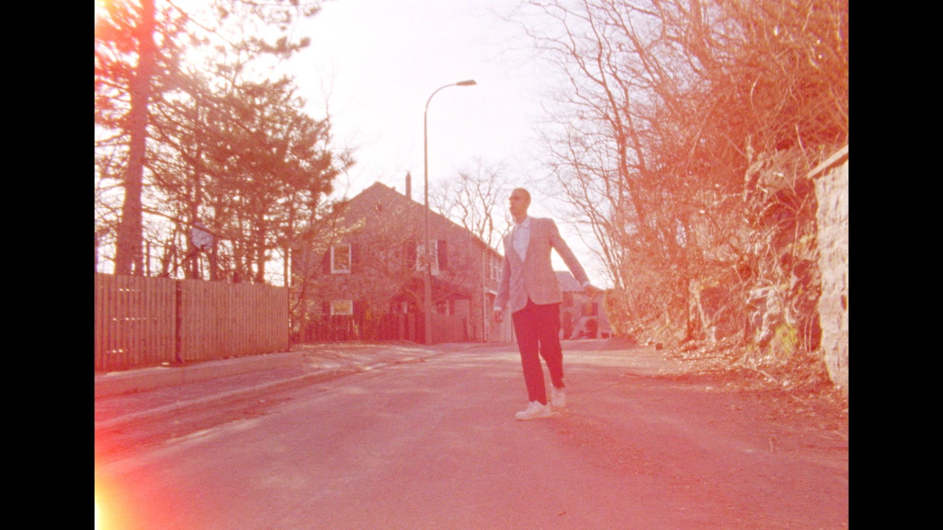 singer Yuki Dreams Again walking in empty street in broad daylight with flare up effect on camera in their promotional video filmed by Les Gamins