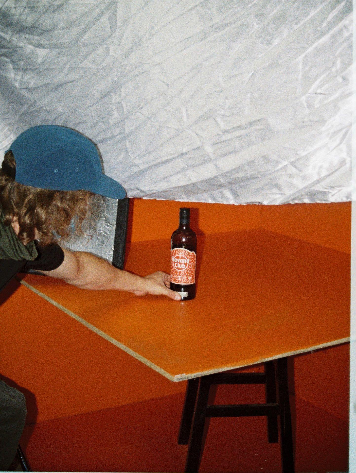 Vincent Ruel-Cote placing bottle of Havana Club brown rhum on orange background for video portrait filmed by Les Gamins for collaboration between Atelier New Regime and Havana Club